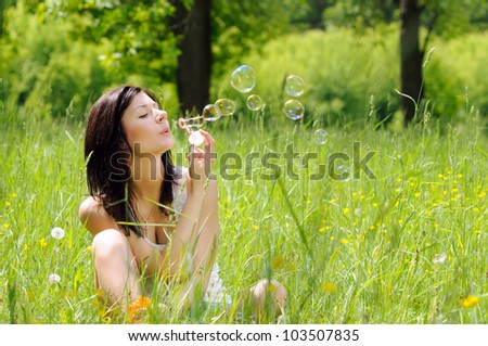 Portrait of young girl inflating soap bubbles on green meadow