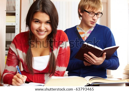 Portrait of young girl looking at camera on background of reading guy in college library