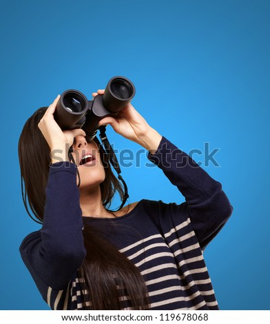 portrait of young girl looking through a binoculars over blue