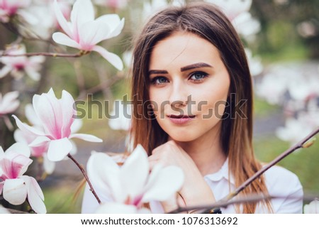 Portrait of young girl near blossom magnolia flowers outdoors in spring park Сток-фото ©