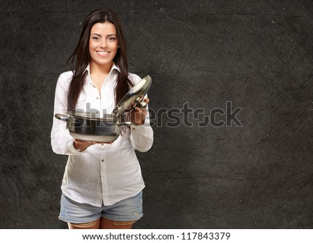 portrait of young girl opening sauce pan against a grunge wall