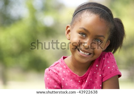 Portrait Of Young Girl Sitting In Park