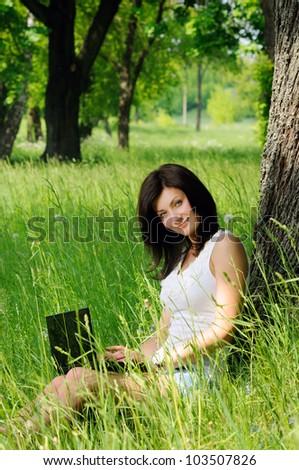 Portrait of young girl sitting with notebook near the tree - stock photo