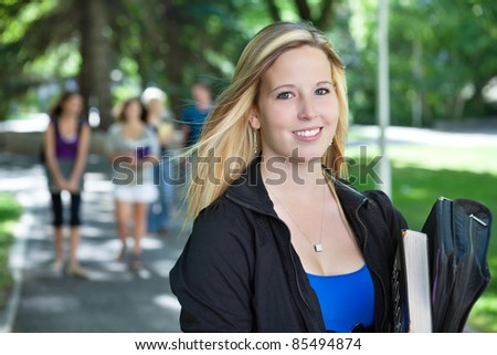 Portrait of young girl smiling with her classmates walking in the background