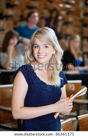Portrait of young girl standing in auditorium with classmates in background