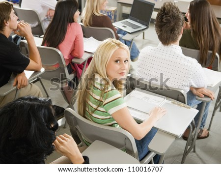 Portrait of young girl studying in classroom with friends in back