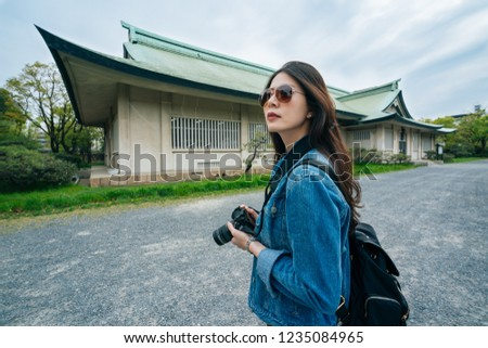 Portrait of young girl tourist holding camera in hands and photographing the old japanese building in osaka. Hipster woman taking photos with retro film digicam on the field. backpacker visit jp.