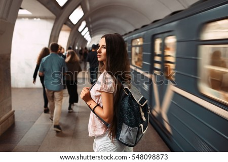 Portrait of young girl with bag pack in metro. Teenager waiting the train of subway.