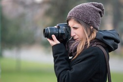 Portrait of young girl with her reflex DSLR taking pictures in a city park - Bologna Giardini Margherita
