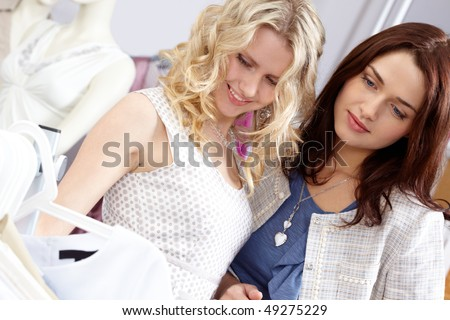 young girls in the department store chosing new clothes - stock photo