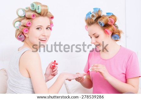 Portrait of young girls wearing pajamas and colorful hair rollers painting nails in red color and smiling at pajama party in the light room