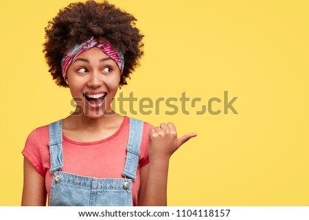 Portrait of young good looking dark skinned female with Afro curly hairstyle, looks joyfully aside, indicates with thumb at copy space, advertises new product, stands against yellow background.