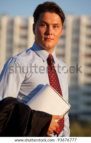 portrait of young good-looking successful businessman holding documants against the constructuin