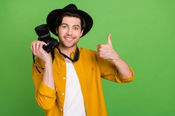 Portrait of young good mood positive cameraman showing thumb-up like feedback isolated on green color background