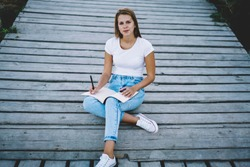 Portrait of young gorgeous female sitting outdoors with notepad , charming hipster girl in denim jeans and white t-shirt with copy space for brandname or label looking at camera resting on weekend