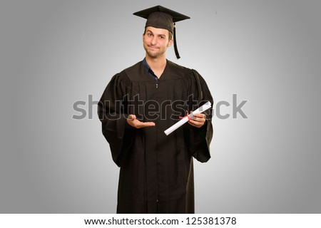 Portrait Of Young Graduation Man Holding Certificate Isolated On Grey Background