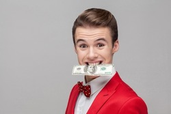 Portrait of young greedy businessman with stylish hairdo in red tuxedo and bow tie holding dollar banknote with teeth, grinning, money-hungry concept. indoor studio shot isolated on gray background