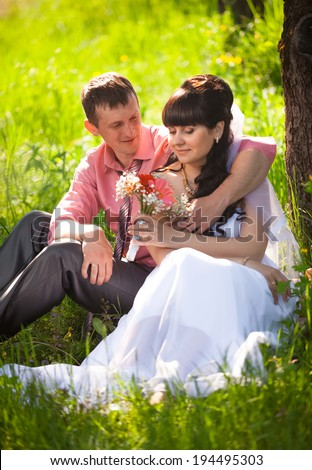 Portrait of young groom presenting flower to bride under tree at park