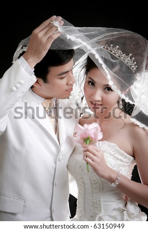Portrait of young groom trying to kiss his bride