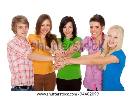 Portrait of young group of people teenagers with their hands piled on top of each other to signal unity and strength, isolated over white background.