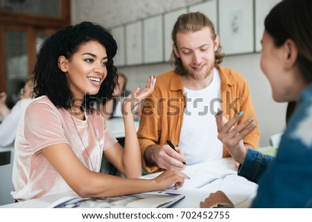 Portrait of young group of people working together in office. Group of students studying together in classroom. Two pretty girls happily talking and discussion something together #702452755
