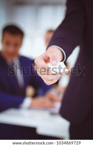Portrait of young handsome business man holding blank white business card - Shutterstock ID 1034869729