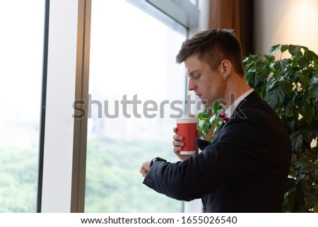 Portrait of young handsome businessman in formal suit enjoying a cup of coffee while checking time.