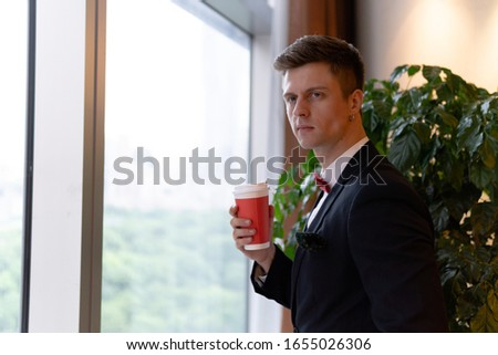 Portrait of young handsome businessman in formal suit enjoying a cup of coffee while looking outside.
