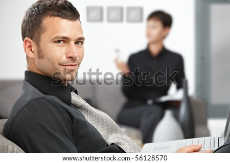 Portrait of young handsome businessman sitting at office lobby, smiling.