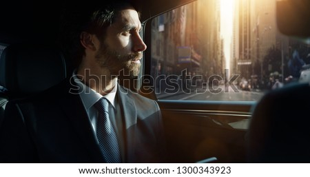 Portrait of young handsome businessman traveling in a modern car with a driver in center of the city by day. Concept of business, success, traveling, luxury  #1300343923