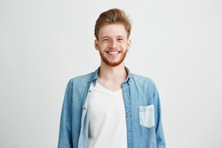 Portrait of young handsome hipster man with beard smiling laughing looking at camera over white background.