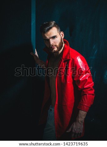 Portrait Of Young Handsome Man. Handsome man wearing red leather jacket on naked muscular torso on dark background, looking on camera #1423719635