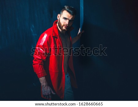 Portrait Of Young Handsome Man. Handsome man wearing red leather jacket on naked muscular torso on dark background, looking on camera