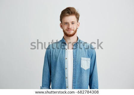 Portrait of young handsome man in jean shirt smiling looking at camera over white background.