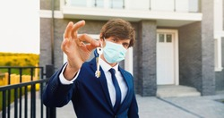 Portrait of young handsome man real-estate agent standing near new house and showing key. Male in medical mask holding house key. Selective focus on hands, close up.
