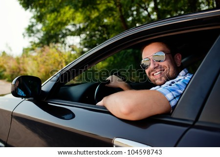 Portrait of young handsome man smiling in his own car