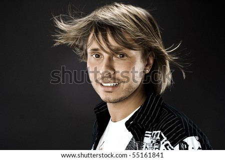Portrait of young handsome man with hair fluttering in the wind on black background in the studio