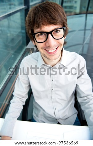 Portrait of young handsome shocked good looking man working using keyboard and looking at camera