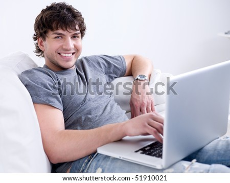 Portrait of young handsome smiling man working on the laptop at home