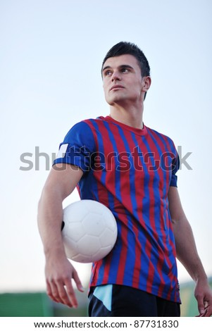 portrait of young handsome soccer player man at football stadium and green grass