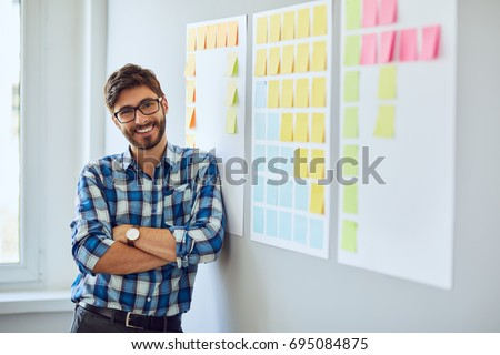 Portrait of young handsome start-up businessman leaning against wall with sticky notes and looking straight at camera