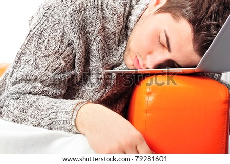Portrait of young handsome student man laying on sofa using laptop for a long time. He is very tired - stock photo