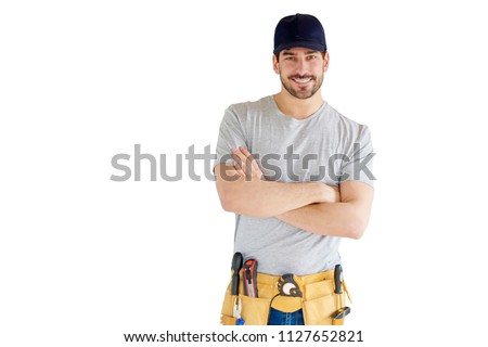 Portrait of young handyman standing with arms crossed standing at isolated white background with copy space. Successful repairman wearing baseball cap and tool belt.