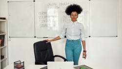Portrait of young happy afro american woman, female teacher standing near whiteboard and looking at camera, teaching Spanish language online from home. E-learning. Distance education. Stay home