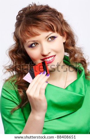 portrait of young happy and dreamy shopaholic woman with credit cards - stock photo