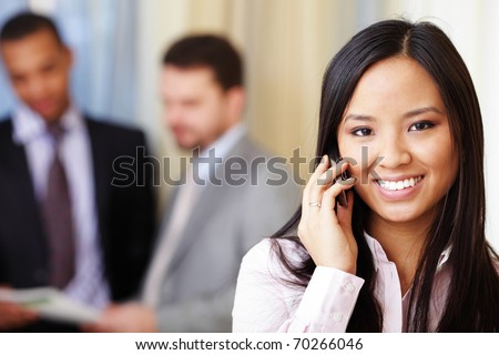 Portrait of young happy asian woman on phone with her business partners on the background - stock photo