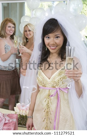 Portrait of young happy bride holding champagne flute with friends in the background