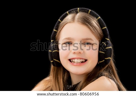 portrait of young happy caucasian blond little girl wearing teeth brackets and sitting in front of black background