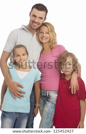 portrait of young happy caucasian family standing together with two kids and smiling over white