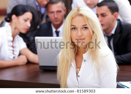 Portrait of young happy caucasian woman with her business partners on the background